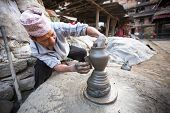BHAKTAOUR, NEPAL - DEC 20, 2013: Unidentified Nepalese man working in his pottery workshop, Dec 20,