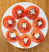 Tasty tomato slices with cheese and anchovies