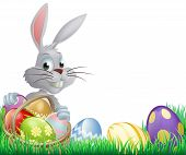 stock photo of ester  - White Easter eggs bunny peeking over a basket of chocolate Easter eggs - JPG