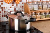 Pot on stove in kitchen on table on mosaic tiles background
