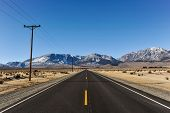 Road To Mountains With Telephone Poles On Side