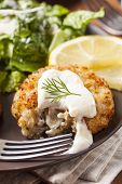 stock photo of crab-cakes  - Organic Homemade Crab Cakes with Lemon and Tartar Sauce - JPG