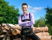 stock photo of lederhosen  - Young man wearing traditional Bavarian lederhosen posing in countryside - JPG