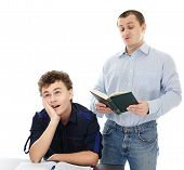 image of boredom  - Studio shot of a teenager sitting at his desk showing boredom while his father is reading loudly isolated over white background - JPG