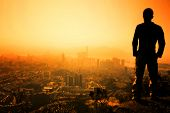 stock photo of mountain lion  - Man standing on the edge of Hong Kong - JPG