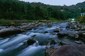 River Water Flowing Through Rocks At Dusk