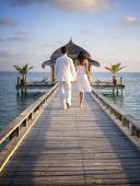 Happy loving couple in white clothes walking on a pier on Maldives