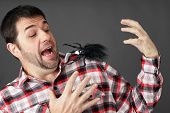 foto of prank  - Prank or arachnaphobia concept: man scared by fake plastic spider on shoulder