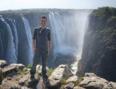 Man posing against Victoria Falls in Zimbabwe, Africa