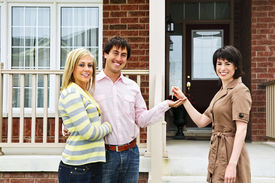 image of real-estate agent  - Happy couple getting keys to new house from real estate agent - JPG