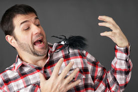 image of prank  - Prank or arachnaphobia concept: man scared by fake plastic spider on shoulder ** Note: Shallow depth of field - JPG