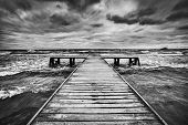 Old wooden jetty, pier, during storm on the sea. Dramatic sky with dark, heavy clouds. Black and whi