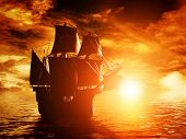 foto of ship  - Ancient pirate ship sailing on the ocean at sunset - JPG