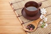 Japanese green tea and sakura branch over mat and bamboo table