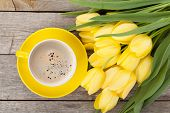 Fresh yellow tulips bouquet and coffee cup over wooden table