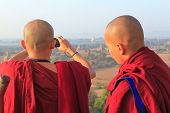 Two monks are enjoy taking photos in front of temples in ancient Bagan city, Mandalay, region of Mya