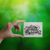 Hand Holding Hand Drawn House On Canvas Board On Green Background As Concept