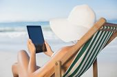Woman relaxing in deck chair on the beach using tablet on a sunny day
