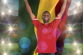 Excited handsome football fan cheering holding ghana flag against large football stadium with brasilian fans