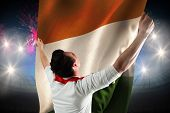 Excited football fan cheering against fireworks exploding over football stadium and ivory coast flag