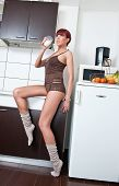 Attractive sexy woman in shirt and socks drinking milk in kitchen. Portrait of sensual girl