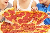 A picture of a group of friends with pizza