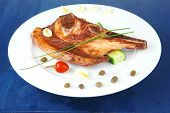 fresh hot roasted beef meat bone steak on ceramic dish with red hot pepper and capers on blue wooden