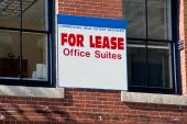 Office Suites For Lease Sign Between Two Windows