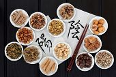 Chinese herbal medicine with yin and yang calligraphy script on rice paper with herb selection.