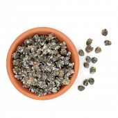 Salted capers in a terracotta bowl and loose over white background.