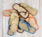 High angle shot of a group of summer beach sandals on a wooden deck. The mulit-colored sandals are a
