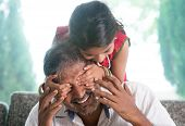 Happy Indian family at home. Asian girl surprising her father by covering daddy eyes. Parent and chi
