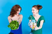 Young women with healthy and unhealthy food like salad and candy in studio