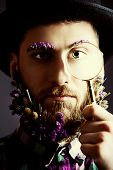 Strange young man with a beard of flowers wearing bowler hat and looking curiously through magnifier