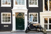 Amsterdam, Netherlands - March 19, 2014:  Vespa Scooter Stands Parked Near Old Living House In Amste