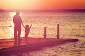 stock photo of dock a lake  - Father and son walking out on a dock at sunset - JPG