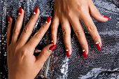 Young woman with fashion red nails against silver sequin background