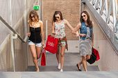 Three beautiful woman walks up the stairs they go shopping