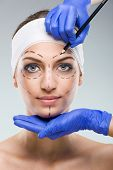 Beautiful woman with plastic surgery depiction plastic surgeon hands