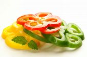 red, yellow and green bell pepper sliced on white background