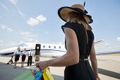 Rear view of rich woman with shopping bags walking towards private jet while pilot and stewardesses