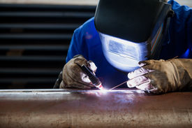 picture of pipe-welding  - Welder in blue suit welding a cilinder pipe - JPG