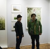Photographer kiiro in front of his pictures at Fotofever 2014, Paris, France