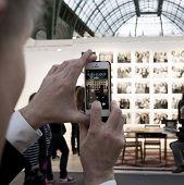 People taking a photo of a photo of Nicholas Nixon at Paris Photo art fair 2014, Paris, France
