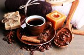Cup with coffee drink, soap with coffee beans and spices, sponge and massage brush on wooden background. Coffee spa concept