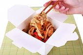 Fried noodle in takeaway box on mat on white background