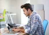 Young man in office working on laptop computer