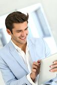 Attractive smiling man with jacket using digital tablet