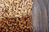 Oats and buckwheat on wooden background