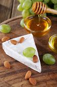 Brie cheese, honey in glass bowl, nuts and grapes on wooden background